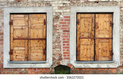Two  windows  with closed locked  wooden blings in the aged brick wall of a ruined  house.  Panoramic collage from several outdoor street photos