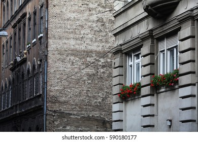 two windows of an old house with red flowers