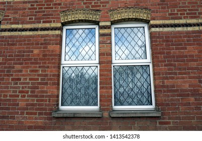 Two windows on the old brick wall with reflection of the sky in England