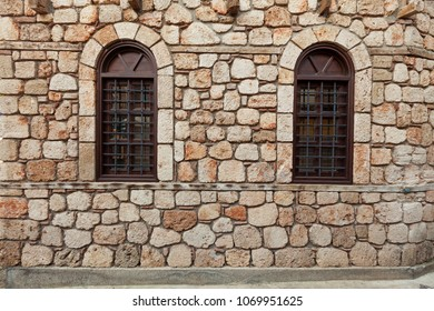 Two windows on old stone wall