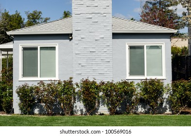 two windows on a side of gray building