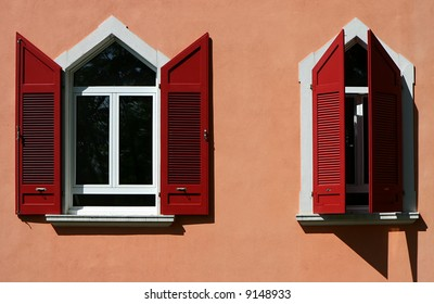 Two windows with red blinds.