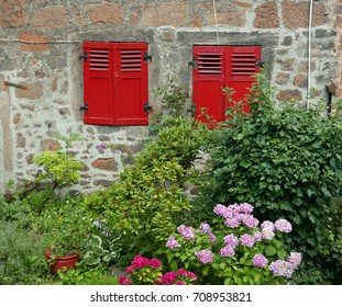Two windows with red wooden shutters in an old stone facade with flower garden in the foreground