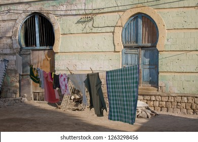 Two windows in a running down house in the historic city of Massawa with a clothes line in front