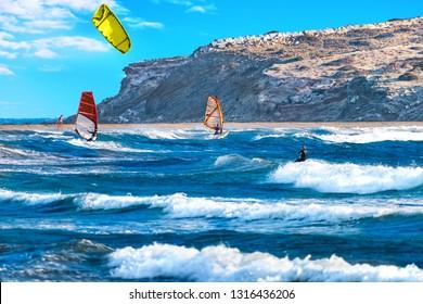 Two windsurfers and kiteboarder ride on Prasonisi beach (Rhodes, Greece)