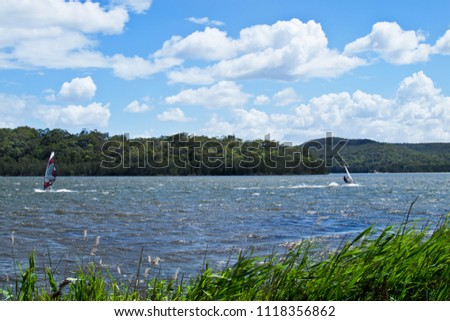Two windsurfers struggling with a strong wind on Narrabeen Lagoon in Sydney.