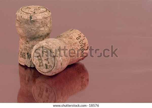 Two wine corks on a reflecting surface