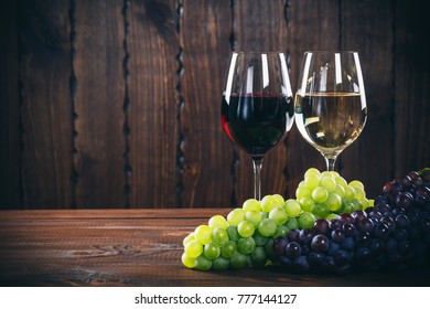 Two wine glass with white and red wine and grapes on wooden background.