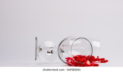 two wine glassed with hearts spilling out of them