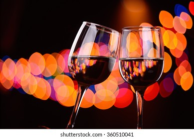 Two wine glasses clink at the party, background with blurred lights