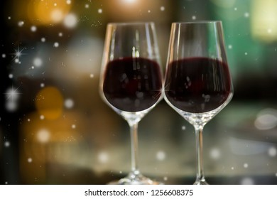 two wine glasses on a bar with snow.