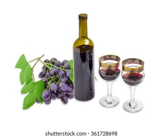 Two wine glasses with red wine, bottle of a wine and cluster of a blue grape with leaves on a light background