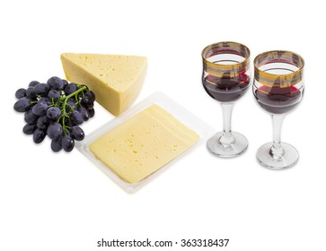 Two wine glasses with red wine, cluster of a blue grape, piece of cheese and several slices of cheese in plastic tray on a light background