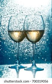 Two wine glasses of toasting against dark blue bokeh background