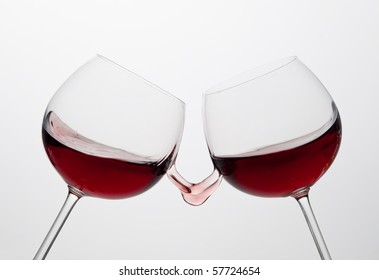 Two wine glasses toasting gesture with splash