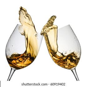 Two wine glasses in toasting gesture with big splashing