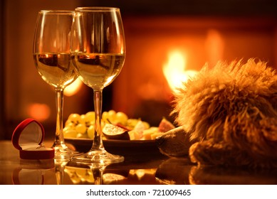 Two  wine wineglasses with the red box with engagement ring over fireplace background.  Romantic concept .