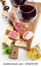 two wineglass with red wine and assortment of cheese and salami. olive oil & basil