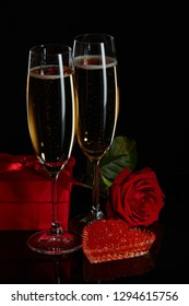 Two wineglasses of champagne, gift box, rose and red caviar on saucer in the shape of a heart standing on a black background. Valentines day