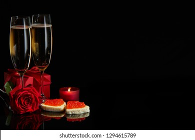 Two wineglasses of champagne, gift box, rose and two canapes with red caviar  in the shape of a heart standing on a black background. Valentines day
