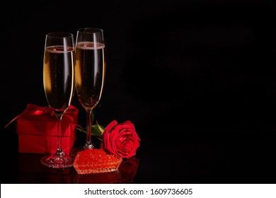 Two wineglasses of champagne, gift box, red rose and red caviar on saucer in the shape of a heart standing on a black background. Valentine's day