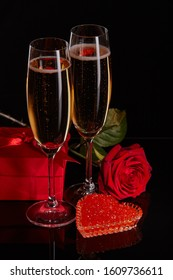Two wineglasses of champagne, gift box, rose and red caviar on saucer in the shape of a heart standing on a black background. Valentine's day