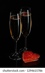 Two wineglasses of champagne and red caviar on saucer in the shape of a heart standing on a black background.