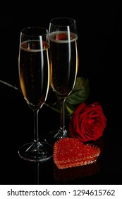 Two wineglasses of champagne, rose and red caviar on saucer in the shape of a heart standing on a black background. Valentines day