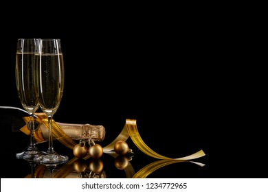 Two wineglasses with champange, bottle and serpentine on a black background with reflection. Copy space. Christmas and New Year background