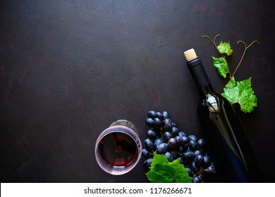 Two wineglasses with red wine, bottle and grape leaves lying on dark wooden background. Top view. Flat lay. Copy space