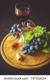 Two wineglasses with red wine and grapes decorated vine leaves on dark wooden desk