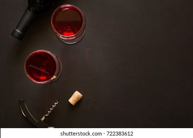 Two wineglasses with red wine and lying bottle on brown wooden desk. Top view.