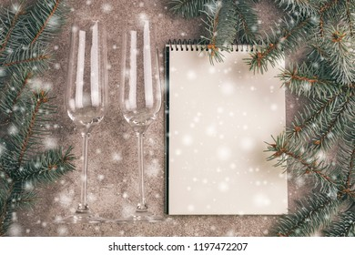 Two wineglasses and scratchpad  for wishes with Christmas decorations - Christmas tree branches on slate marble background with snow effect. Top view. Copy space. Flat lay
