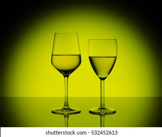 Two wineglasses with white wine on blurred yellow round background