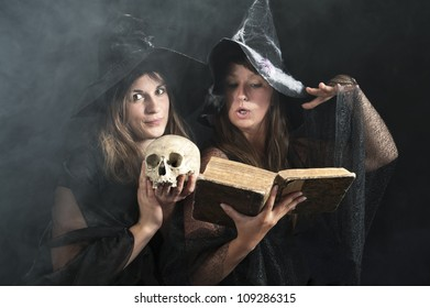 two witches with a book and skull