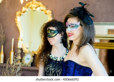 two woman with black hair and a masquerade mask posing on a brown background
