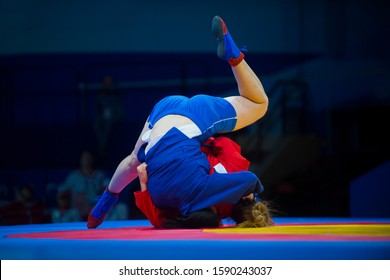 Two woman in blue and red wrestling on a yellow wrestling carpet in the gym