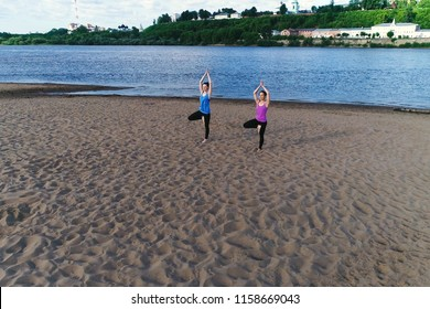 Two woman doing yoga on the beach by the river in the city. Beautiful view. Vrikshasana pose.