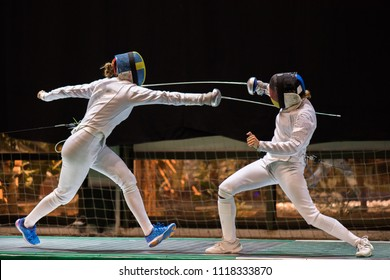 Two woman fencing athletes fight on professional sports arena