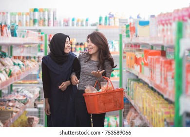 two woman friend buying some stuff at grocery store together