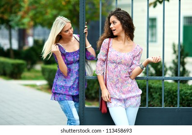 two woman friends outside smiling
