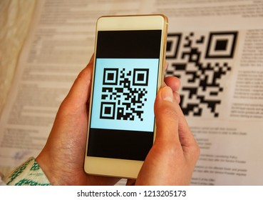 Two woman hands holding cellphone and scanning QR code, Cashless payment