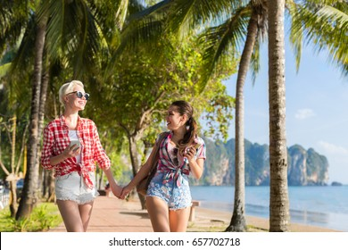 Two Woman Hold Hands Walking In Tropical Palm Trees Park On Beach, Beautiful Young Female Couple On Summer Vacation Tourists Holiday Travel