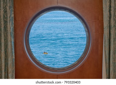 Two woman in a kayak on the open ocean as seen through the porthole of a cruise ship