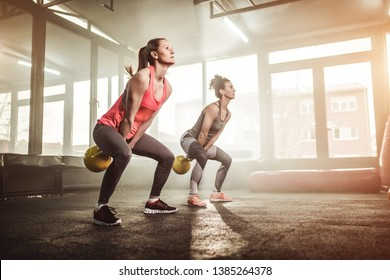 Two woman lifting kettle-bell in cross fit gym