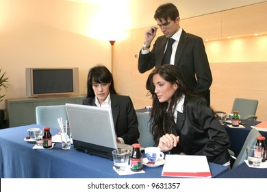 two woman and a man in a meeting room