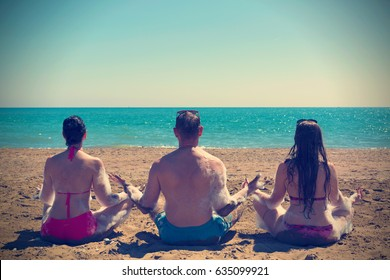 Two woman and man in yoga poses sitting on the beach