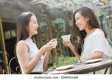 Two woman meet in coffee shop talk without use smartphone