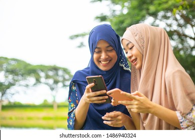 Two woman muslim play social media with smartphone in the outside.