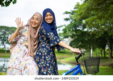 Two woman muslim ride bicycle for travel in the garden.